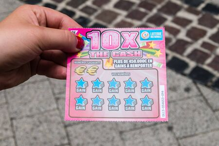Luxembourg, Luxembourg - June 5, 2019: Loterie Nationale 10 x The cash lottery scratch card in woman hand. Redactioneel