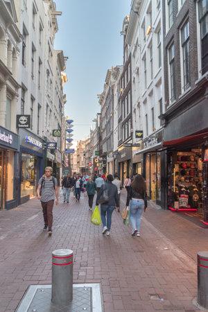 Amsterdam, Netherlands - June 6, 2019: Pople on Kalverstraat street. Kalverstraat is a busy shopping street of Amsterdam.