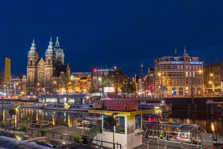 Amsterdam, Netherlands - June 6, 2019: Canal and buildings over canal with The Basilica of Saint Nicholas at night.