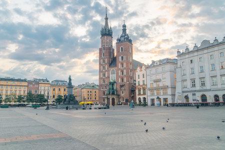 Krakow, Poland - July 26, 2019: Market square with famous saint Marys Basilica at sunrise.