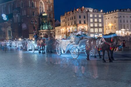 Horse carriages at Main Square in Krakow at night, Poland.