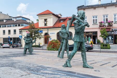 Wieliczka, Poland - July 27, 2019: Sculptures of medieval salt mine workers at the main market square.