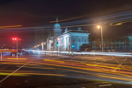 Blurred motion long exposure lines light of car headlamps headlights at night. Street view of city center of Dublin with The Custom House in background in Dublin, Ireland. Reklamní fotografie