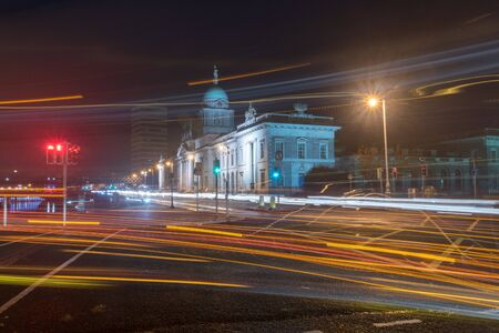 Dublin, Ireland - November 5, 2019: Blurred motion long exposure lines light of car headlamps headlights at night. Street view of city center of Dublin with The Custom House in background in Dublin, Ireland.