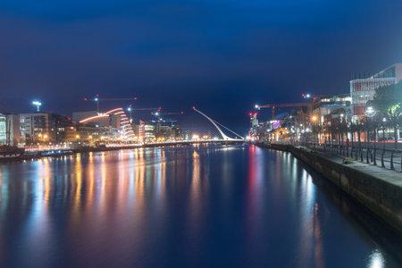Dublin, Ireland - November 5, 2019: Liffey river with Samuel Beckett Bridge at night.