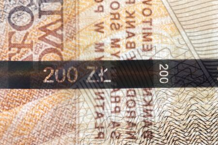 Plastic security strip inside 200 PLN banknote. Security strip on Polish banknote created to prevent counterfeiters.