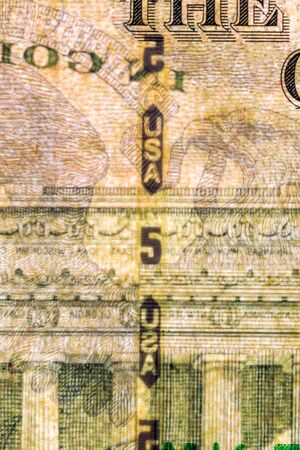 Plastic security strip inside 5 USD banknote. Security strip on American banknote created to prevent counterfeiters.