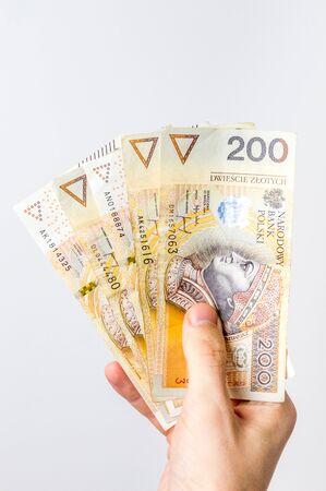200 polish zloty bills held in hand.