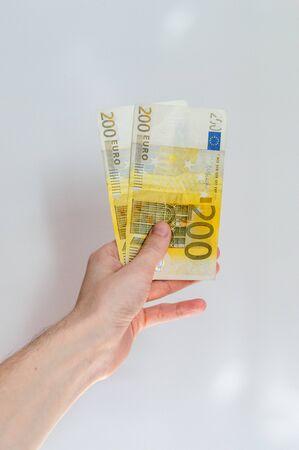 200 Euro bills held in hand.