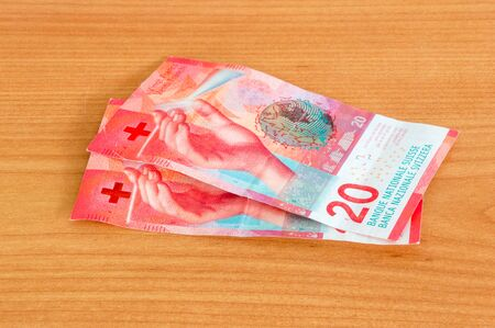 Swiss Francs (20 CHF) banknotes on wooden table.
