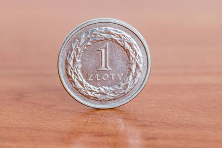 Polish 1 zloty coin on wooden table.