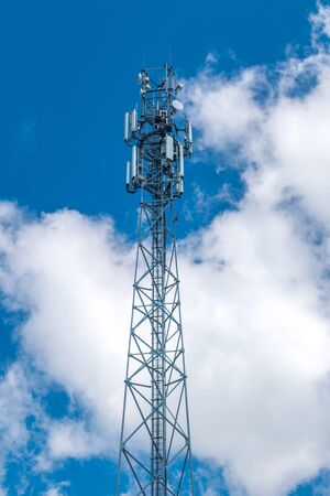 Telecommunication tower on blue sky with clouds.