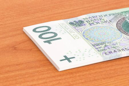 Close-up of part of stack of 100 PLN banknotes.