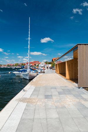 Mikolajki, Poland - June 1, 2020: Summer view on pavement along marina on Mikolajskie lake. Publikacyjne