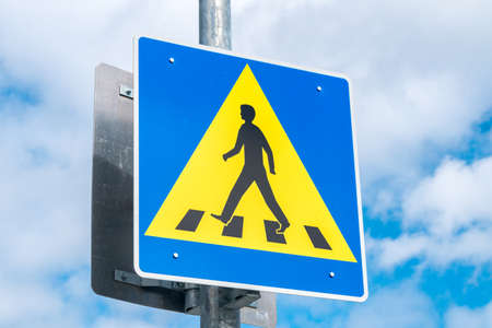 Pedestrian road sign on cloudy sky.
