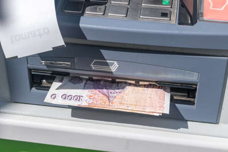 Reykjavik, Iceland - June 20, 2020: Withdraw money from ATM. 100 ISK banknotes at ATM machine.