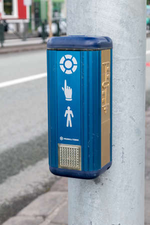 Reykjavik, Iceland - June 20, 2020: Pedestrian touch button for crossroad with traffic lights in Iceland.