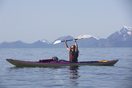 kayaker: A female sea kayaker paddles her boat through Humpy Cove near Seward, Alaska