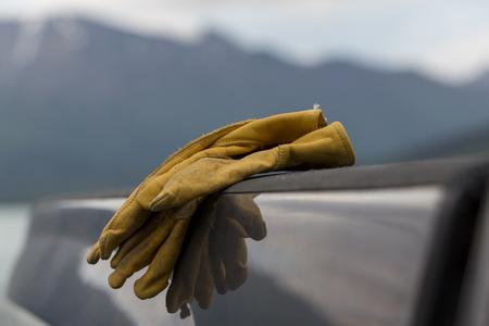 camioneta pick up: Un par de guantes de trabajo de cuero marr�n que se sienta en la cama de una camioneta gris.