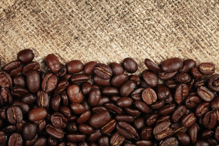 Coffee beans on burlap background. Stock Photo