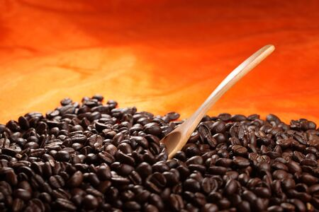 Coffee beans with wood spoon on orange background. Stock Photo - 11819934