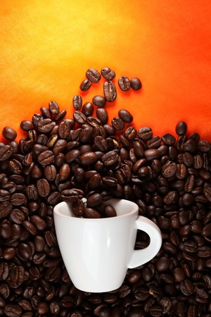 Coffee cup with beans on orange background. photo