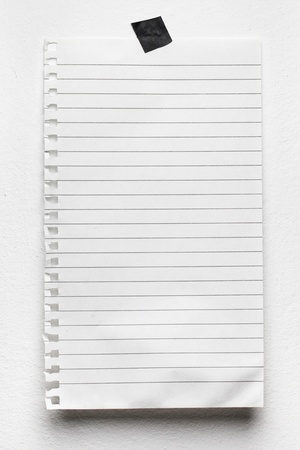 Notepad page on white wall. photo