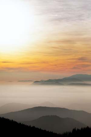 A colorful sunset with foggy mountain layers