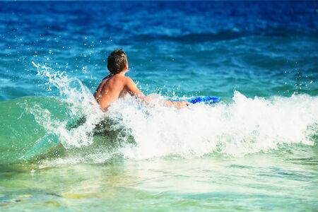 Little boy learning surf in blue sea  Stock Photo