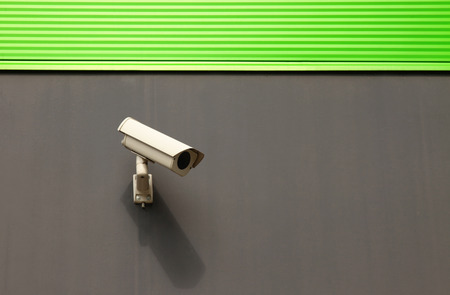 Security camera on a building with new green facade  Stock Photo