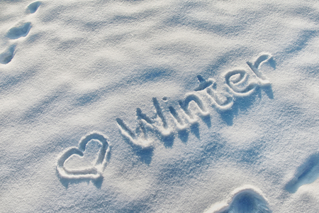 Winter word message with heart on the snow
