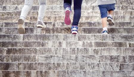 Kinderen (alleen poten) lopen op stenen stad trappen.