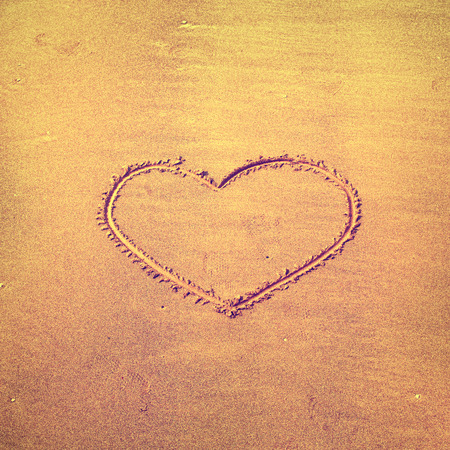 Single love heart sign on sand beach. Vintage filter effect used. Stock Photo