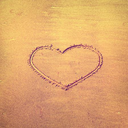 Solo muestra del coraz�n el amor en la playa de arena. Efecto de filtro utilizado vendimia.