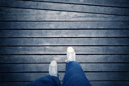 walking boots: White foot on shoes from an aerial view on blue colored wooden background. Point of view man walking on aged blue color wooden floor with place for text message. Blue color filter effect and vignetting used. Stock Photo