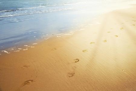 Huellas en la arena con la luz del sol. Foto de archivo
