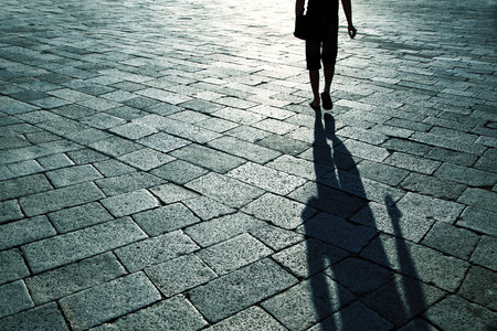 shadow man: Shadow of single man with cigarette in right hand walking on cobbled street.