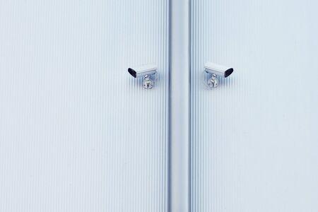 big brother spy: White security camera devices on light blue building. Foto de archivo