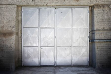defense facilities: Aged stainless steel or chrome metal door and metal wall. Stock Photo