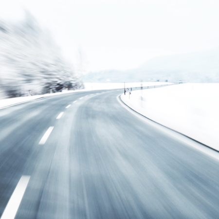 winter road: Blurred dangerous and fast turn at the icy snow road. Motion blur visualizies the speed and dynamics.