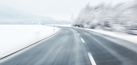 snow road: Blurred danger and fast turn at the icy snow road. Motion blur visualizies the speed and dynamics. Stock Photo