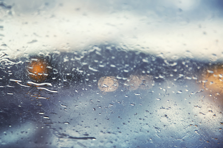 peligro: Coche peligroso conducir con visibilidad limitada cuando se conduce a través de una tormenta de lluvia. Resumen gotas de lluvia borrosas de la salpicadura en el parabrisas de un coche en la carretera ocupada de tráfico.