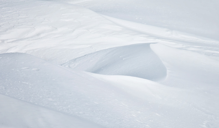 Abstract detail of drifting snow catching late afternoon light showing blurry gentle ridges with soft highlights and shadow. Foto de archivo