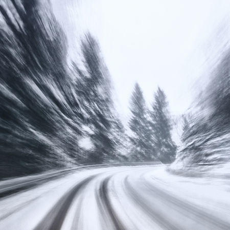 Danger turn at the heavy snow road. Motion blur visualizies the speed and dynamics.