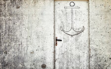 contryside: Anchor sign on old grunge door. Vintage filter effect used. Stock Photo