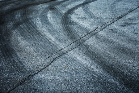 squeal: Abstract asphalt road background with crossing of tires tracks.