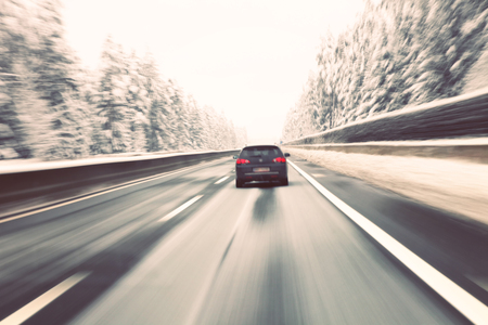 Vintage blurry black car high speed driving on icy winter highway. Motion blur visualizies the speed and dynamics.