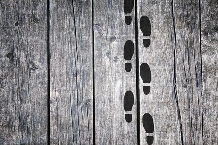 shoeprint: Black silhouette shoeprints on aged wooden background. Black color shoeprints on old wooden floor.
