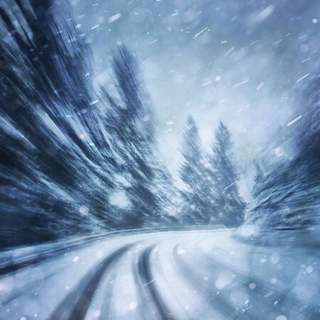 danger: Danger turn at the heavy snowfall road. Motion blur visualizies the speed and dynamics.