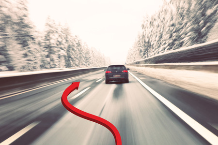 overtaking: Dangerous overtaking cars on the road with added illustrated red arrow (concept). Vintage blurry black car high speed driving on icy winter highway. Motion blur visualizies the speed and dynamics. Stock Photo